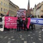 """Man sieht eine kleine Demonstration gegen eine AfD-Kundgebung in Altenburg (Thüringen). Vorne eine Israel-Fahne, eine Regenbogen-Fahne und ein Transparent mit der Aufschrift: """"Rassistisch. Sexistisch. Neoliberal. AfD: Partei fürs Kapital. Nationalismus ist keine Alternative."""""""