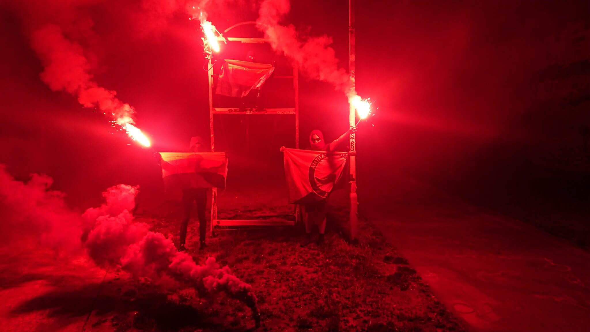 Drei Aktivist*innen mit Pyro-Fackeln, zwei Rojava-Fahnen und einer Antifa-Fahne