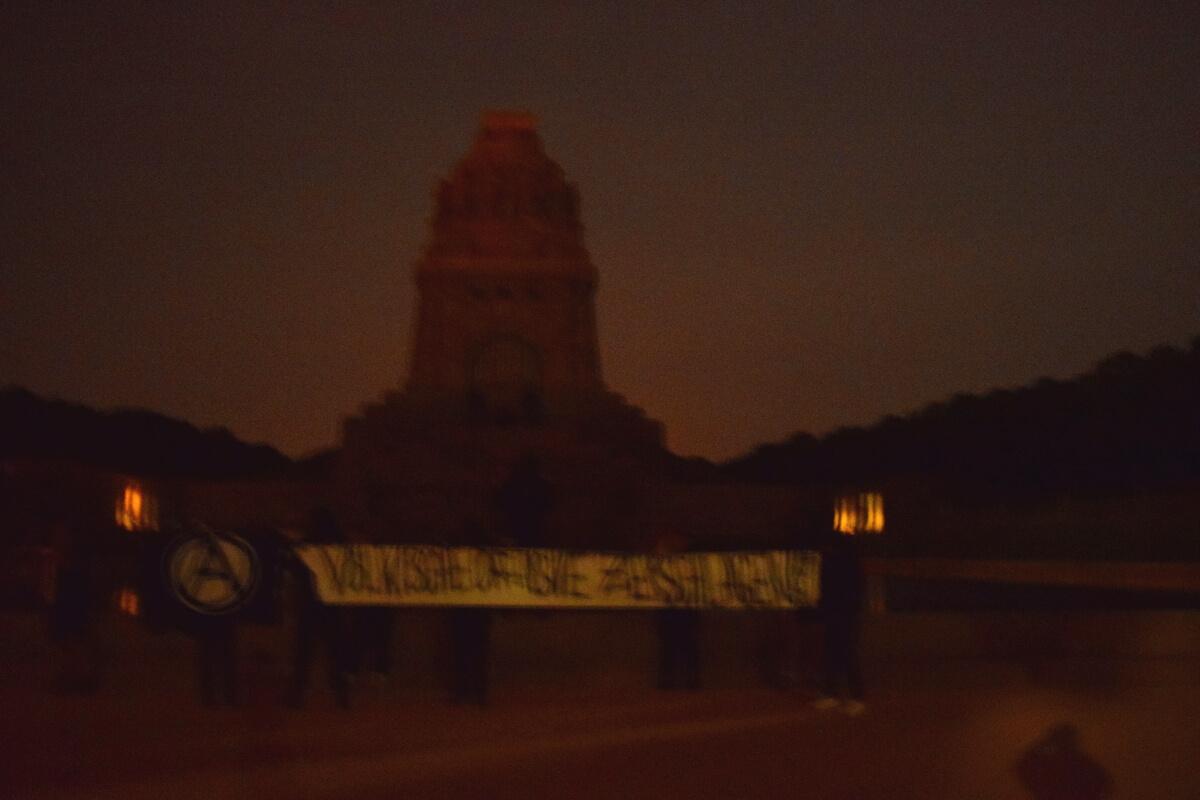 """Völkerschlachtdenkmal und davor ein Transparent mit Aufschrift: """"Völkische Offensive zerschlagen!"""""""